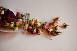 Dried roses falling out of a clear glass jar