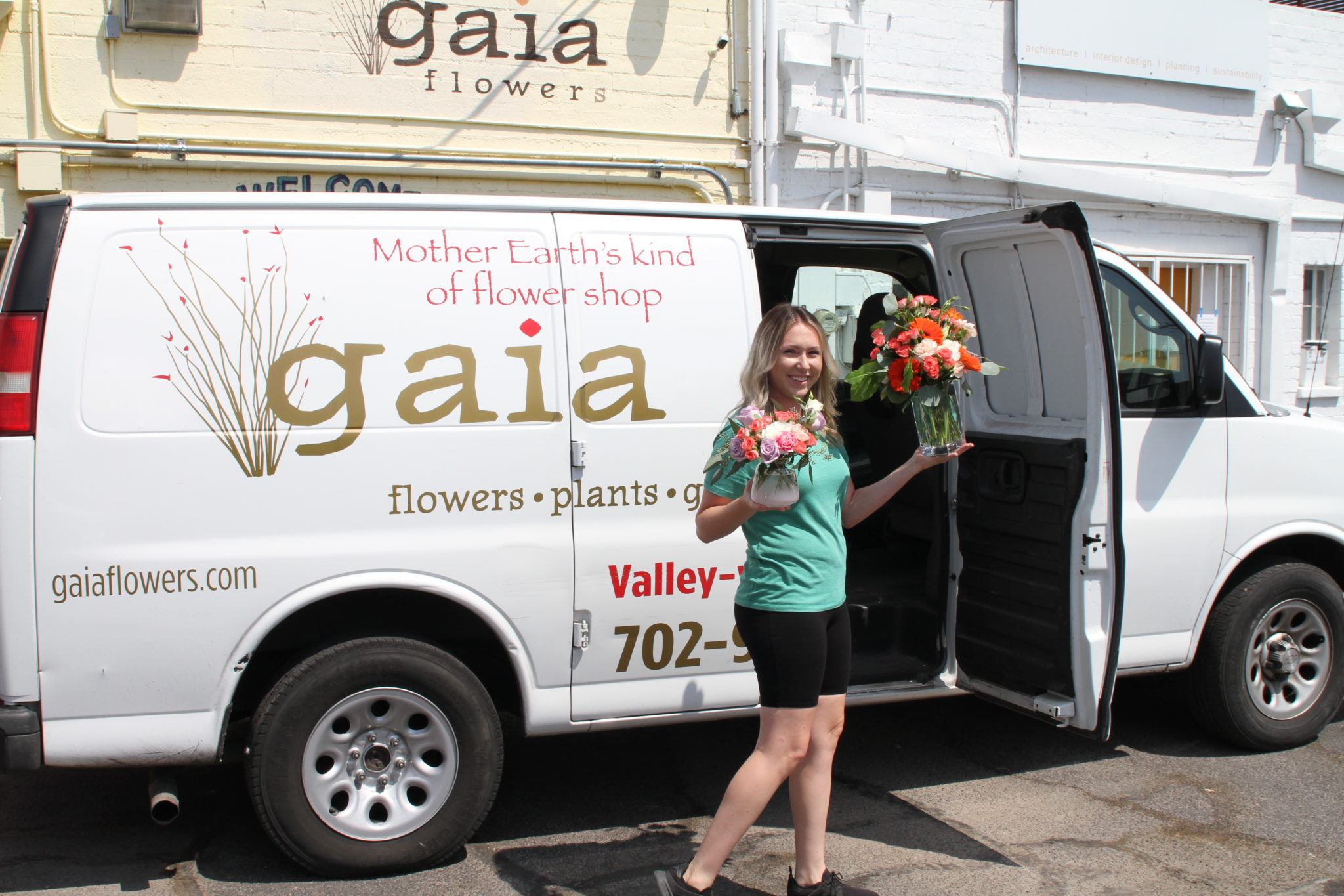 Lauren stands near Gaia Flowers van ready to deliver flower subscriptions.