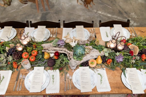 Green succulent wedding centerpiece in branch and surrounded by colorful vegetables.