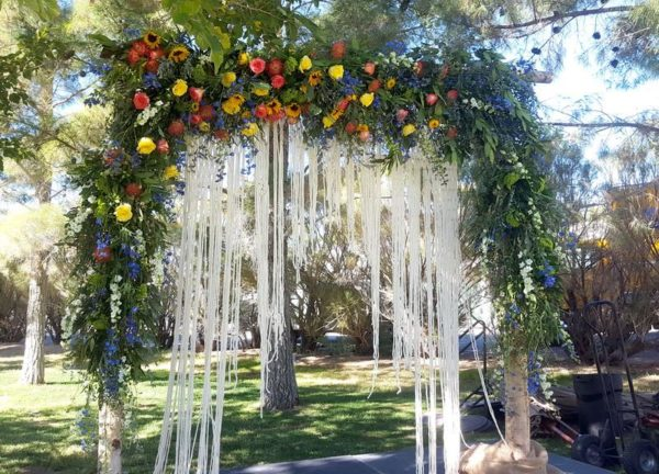 Wedding arbor of greenery and flowers.