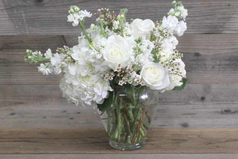 Tulips, carnations and seasonal foliage, all tied together and presented in a glass vase.