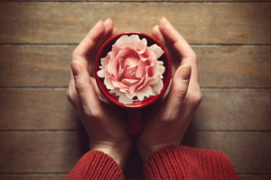 Woman holding hot cup of coffee with flower in the cup.