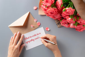 Woman writing sympathy card on gray table with bouquet of pink roses.